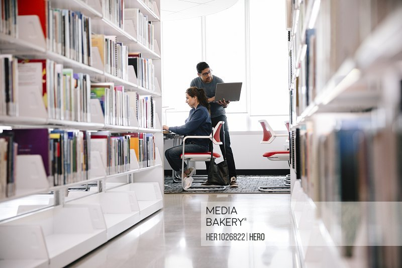 Student working at desk with friend using laptop in univerity library