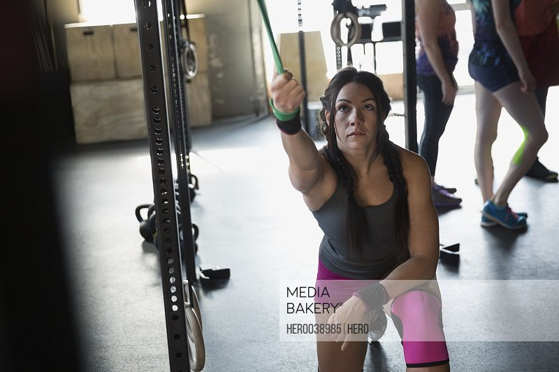 Focused woman using resistance band at gym