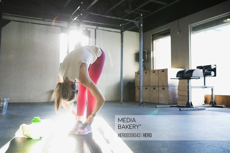 Woman stretching in forward fold at gym
