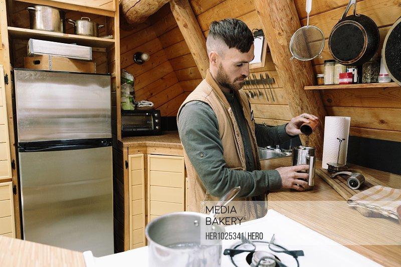 Man preparing coffee in cabin kitchen