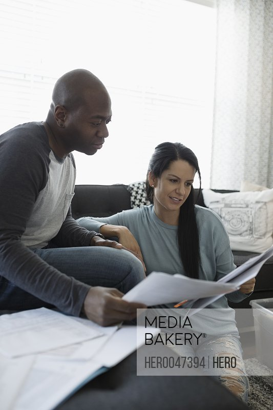 Couple reviewing financial paperwork on living room sofa