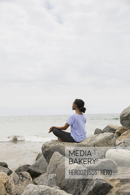 Serene woman sitting in lotus position beach rocks