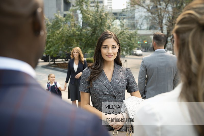 Portrait confident young businesswoman on urban sidewalk