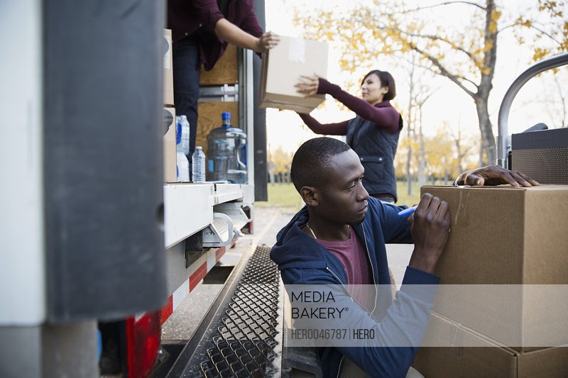 Volunteer writing on cardboard box outside truck