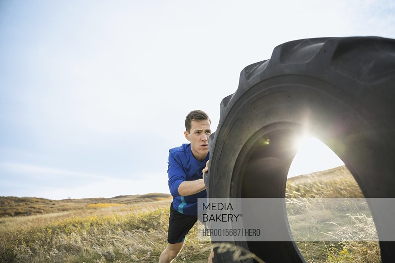 Man pushing crossfit tire in sunny rural field