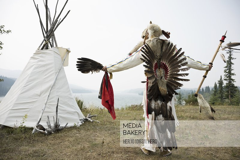 Native American Indian in traditional clothing outside teepee