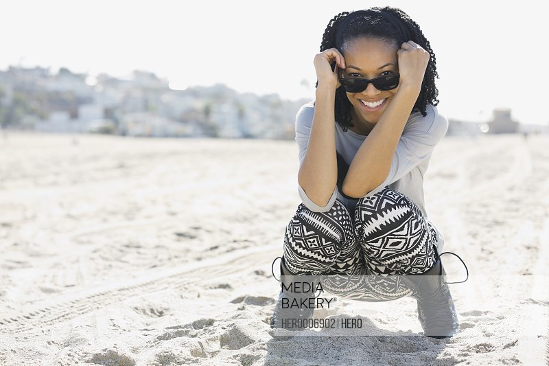 Woman crouching on sandy beach