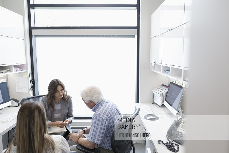 Female doctor talking with senior male patient in clinic office