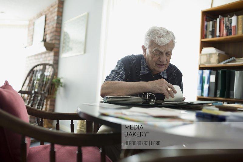 Senior man looking through photograph album