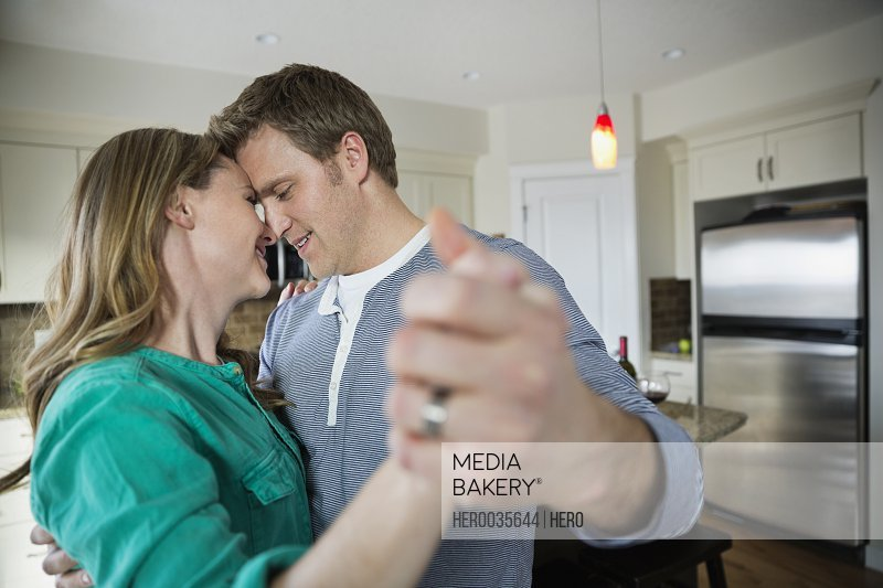 Romantic mid adult couple dancing in kitchen.