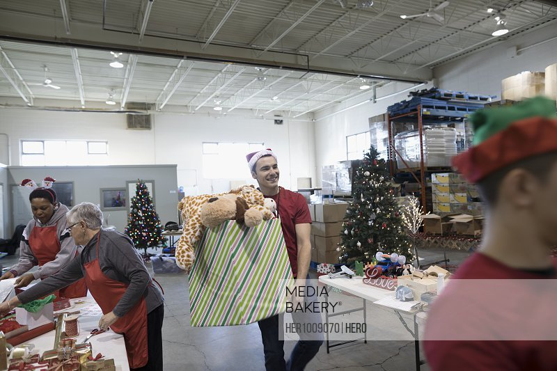 Male volunteer carrying box of Christmas toys in warehouse