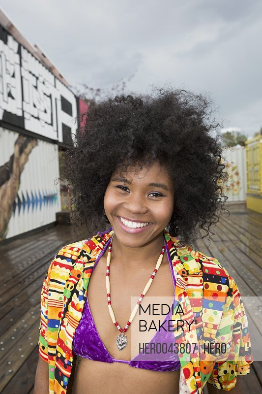 Portrait smiling young woman with curly back afro in bikini