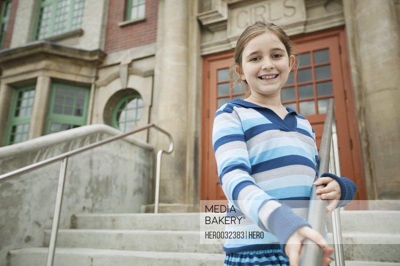 Female elementary student outside school building