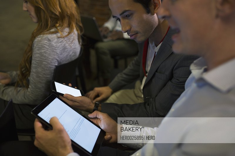 Businessmen using digital tablet in conference audience