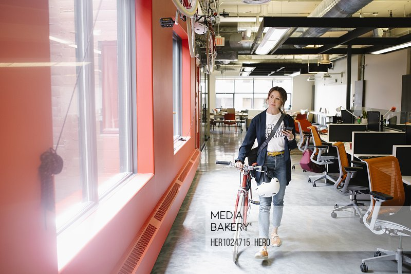 Creative businesswoman with bicycle and smart phone walking in open plan office