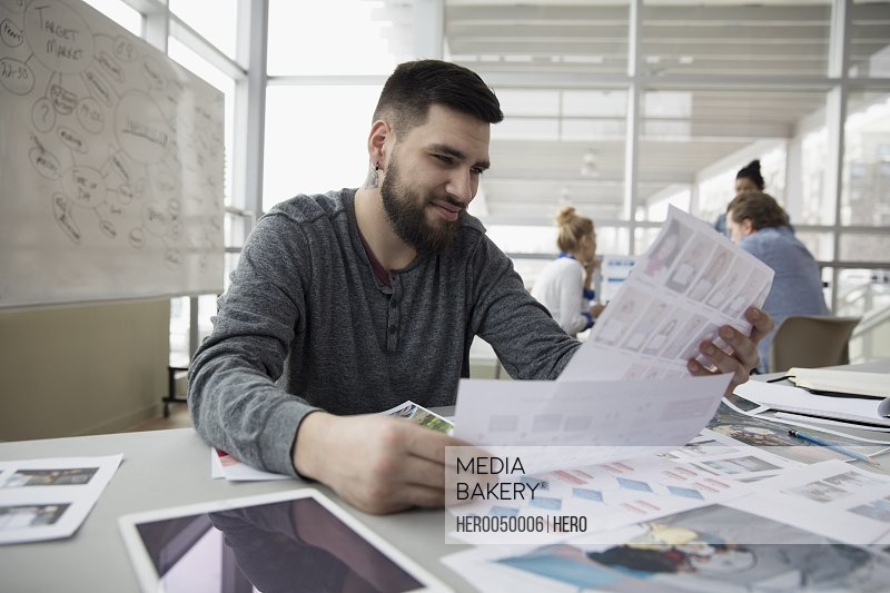 Creative male designer reviewing proofs in office