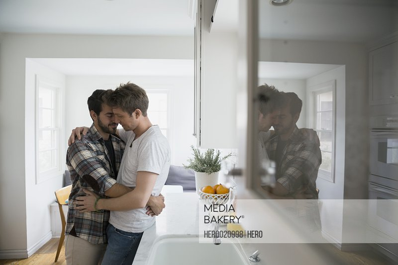 Affectionate homosexual couple hugging in kitchen