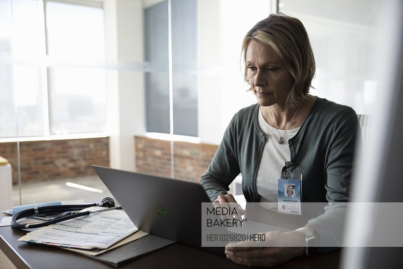 Mature female doctor sitting at desk and using laptop