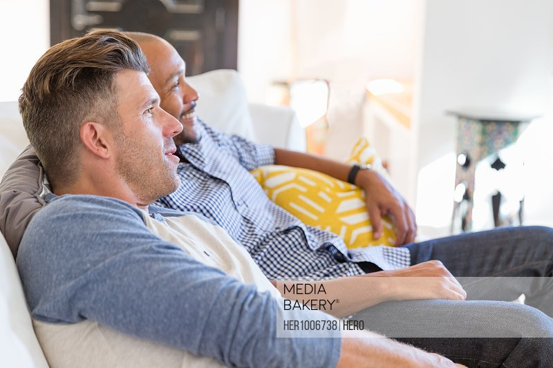 Male gay couple relaxing, watching TV on living room sofa