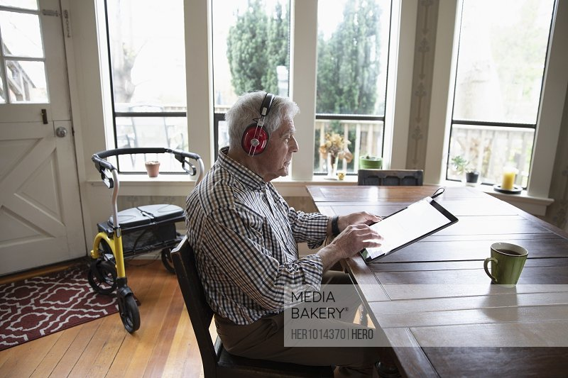 Senior man with headphones using digital tablet at dining table