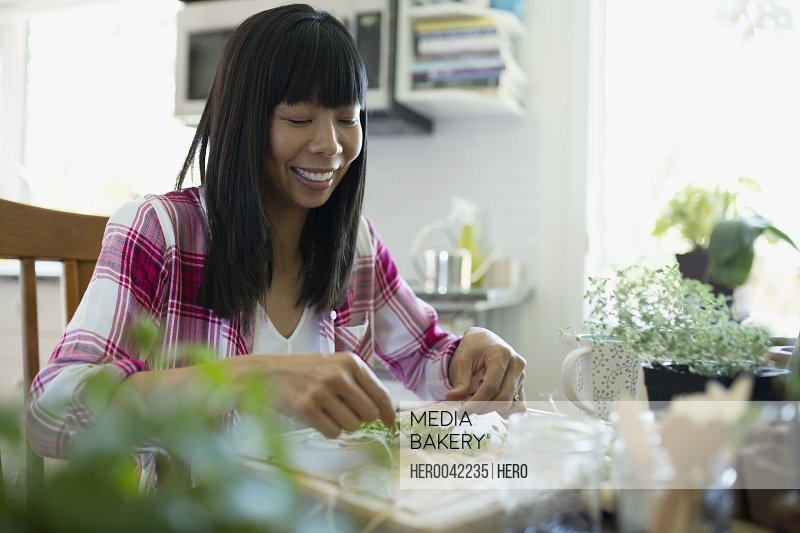 Smiling woman drying herbs at kitchen table