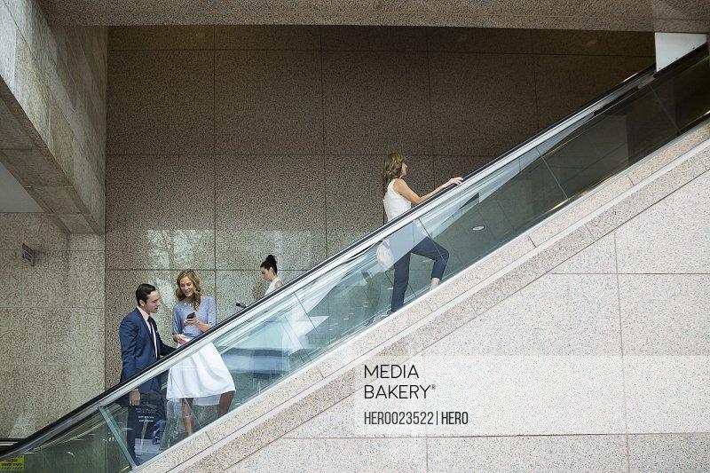 Business people riding escalator
