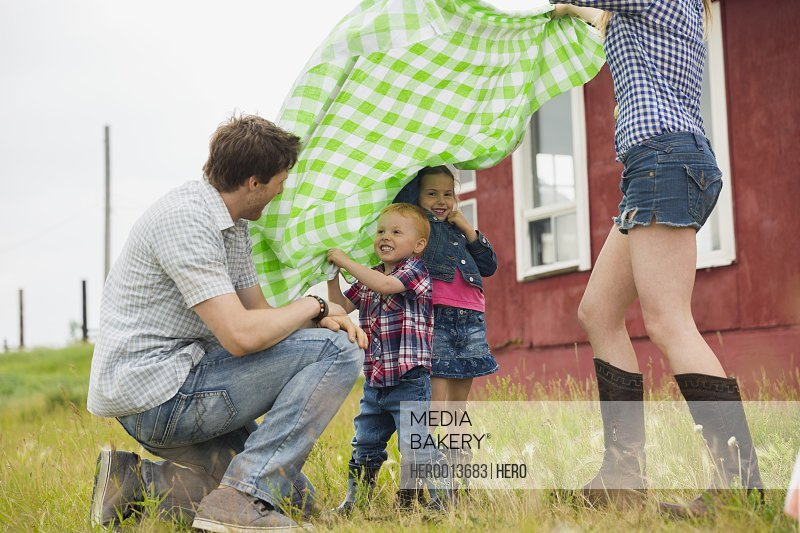 Family with picnic blanket in rural field