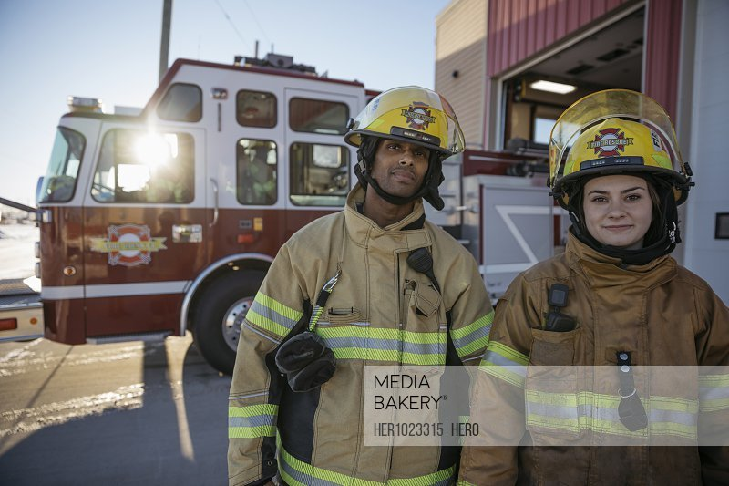 Portrait smiling firefighters outside fire station