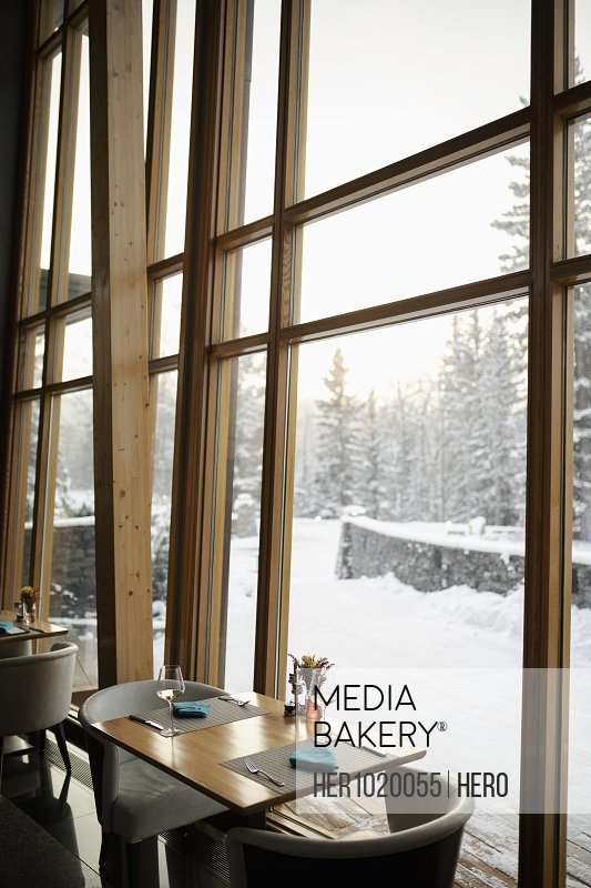 Restaurant table by window with snowy view