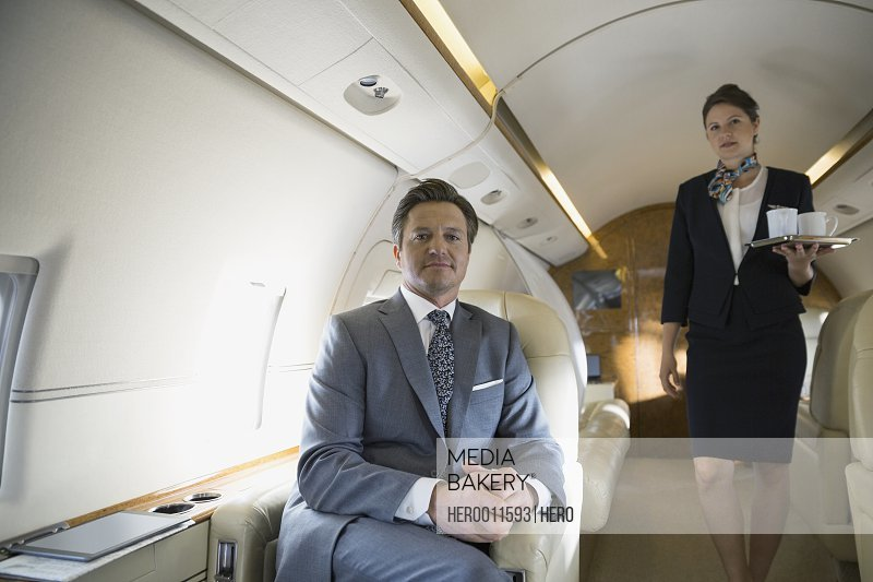 Businessman and flight attendant on corporate jet