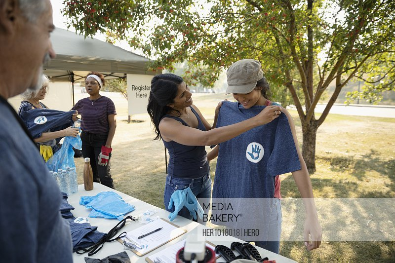 Mother and daughter volunteers checking in at table in park, receiving t-shirt