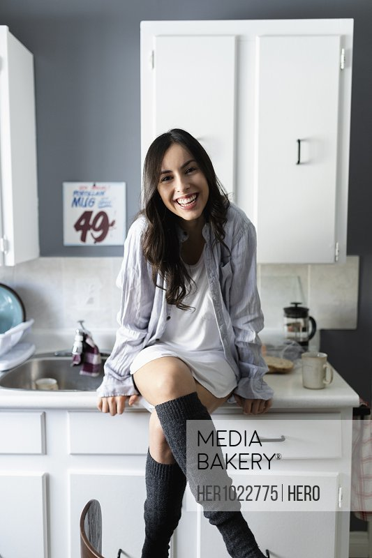 Portrait happy young Latinx woman sitting on kitchen counter