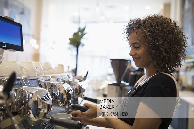 Smiling female barista making coffee at espresso machine in cafe