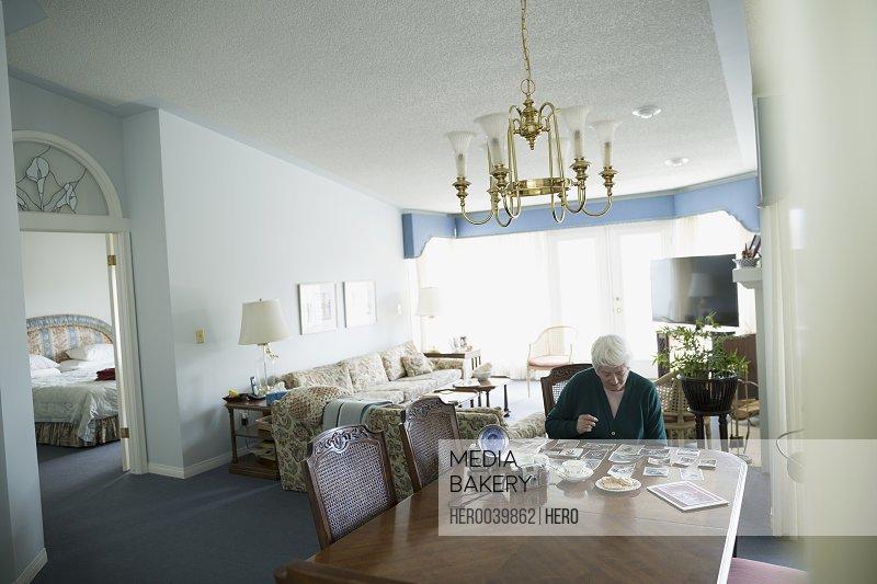 Senior woman looking at old photographs at dining room table