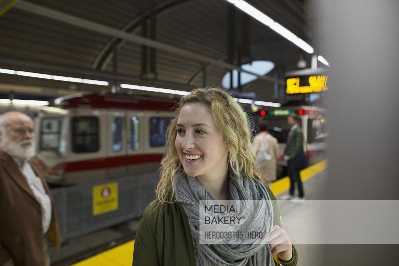 Smiling woman on subway station platform