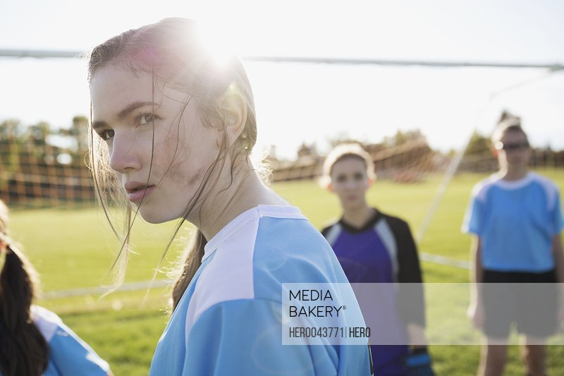 Serious middle school girl soccer player showing attitude on sunny field