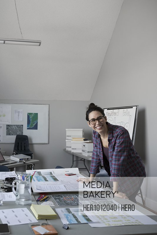Portrait smiling, confident female city planner reviewing blueprints, working in office