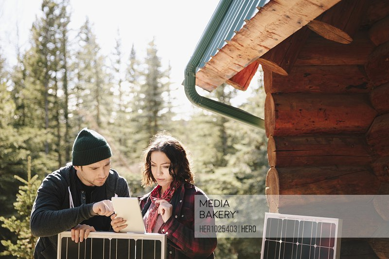 Couple using digital tablet, installing solar panels outside cabin