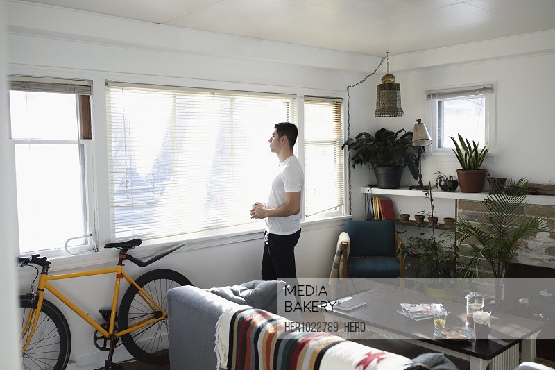 Thoughtful young Latinx man looking out sunny living room window