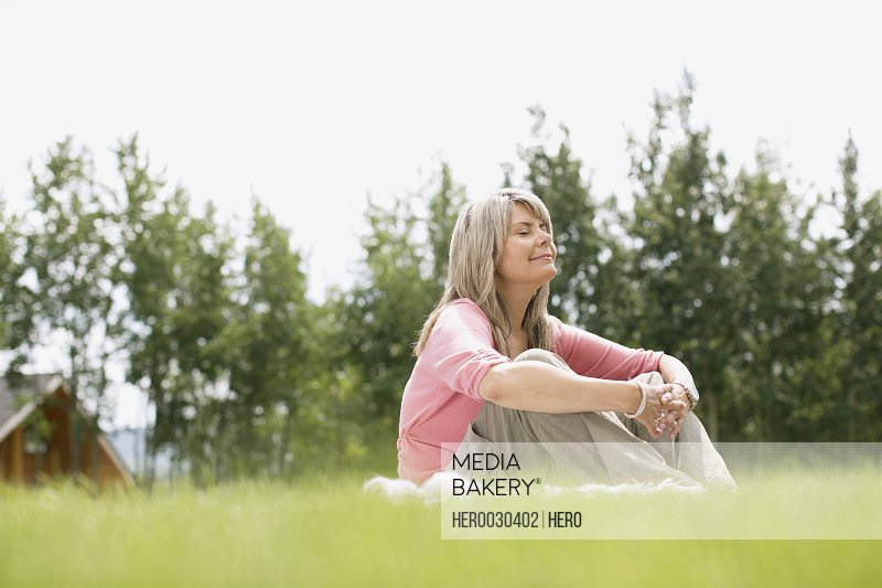 middle aged woman sitting outdoors in grass