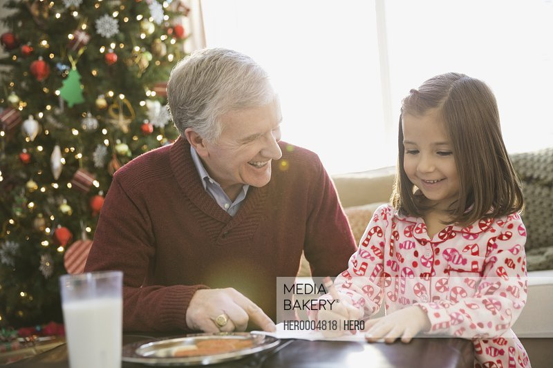 Grandfather helping girl write letter to Santa Claus