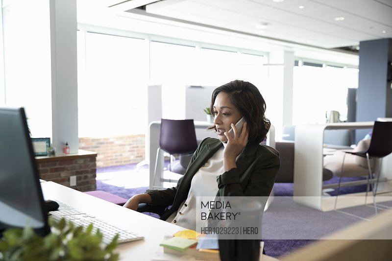 Mid adult businesswoman on cell phone in open plan office