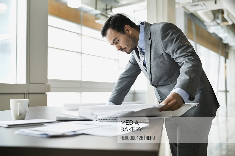 Businessman looking at blueprints in office building