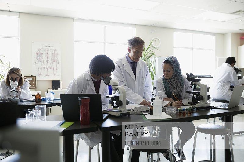 Professor helping students conducting scientific experiment in laboratory