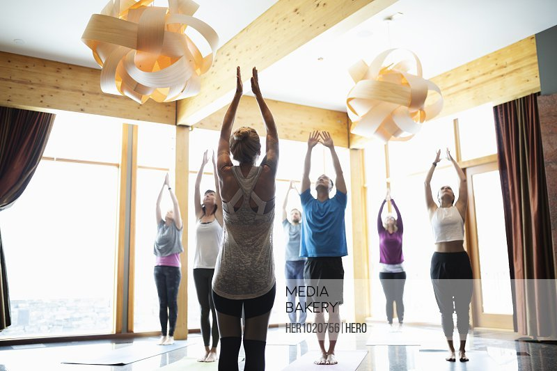 Instructor leading yoga class in studio