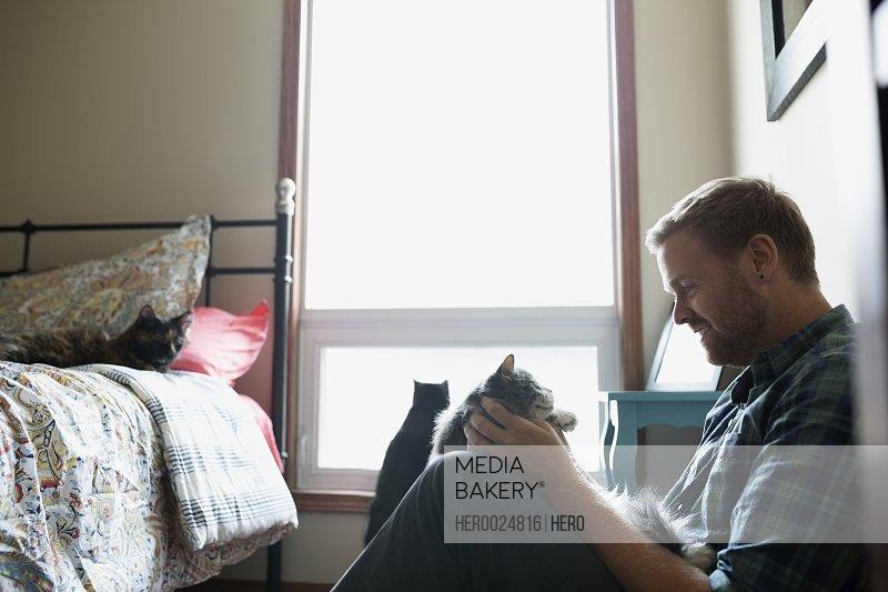 Man Petting Cat In Bedroom