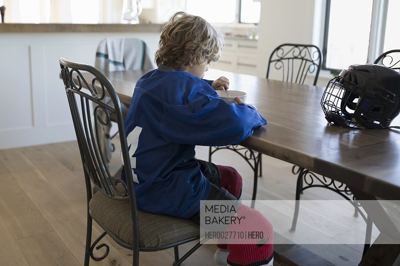 Boy in ice hockey uniform eating cereal table