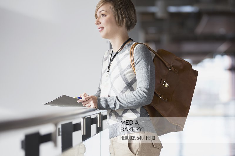 Businesswoman holding paperwork and briefcase