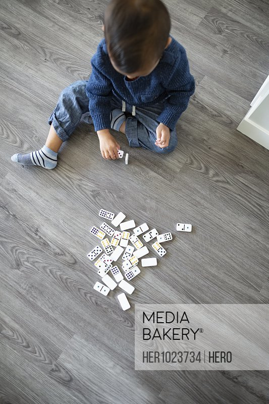 Boy playing with dominos on floor