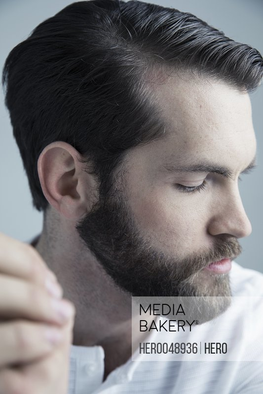 Close up profile portrait serious brunette Caucasian young man with beard looking down